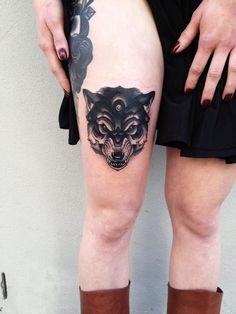 Angry black wolf head tattoo on the left thigh