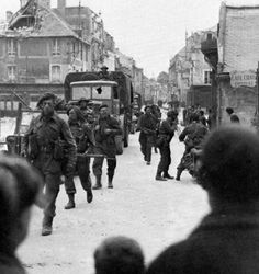 British 4th Brigade Commandos tramp through a village between Sword and Juno Beaches. Normandy, France, June 1944.