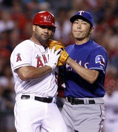 Texas Rangers relief pitcher Koji Uehara, of Japan, right, tags out Los Angeles Angels' Albert Pujols on a ground ball in the in the eighth inning of a baseball game in Anaheim, Calif.,  on Friday June 1, 2012. The Angels won 4-2. (AP Photo/Christine Cotter)  game 52