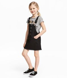 Black. Bib overall dress in stretch cotton twill with metal snap fasteners on bib section. Adjustable suspenders with metal buckles, front pockets, and back
