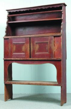 New York State 18th Century Court Cupboard, original red paint, graduated open top with scalloped cut outs and beaded plate rail above two paneled sliding doors and open bucket bench base, 72.5 H. x 49 W. x 14 D.