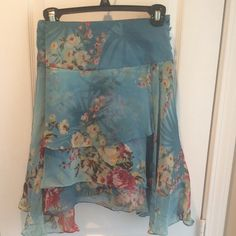 Silk Floral Skirt with layers Size 12 silk floral skirt with fluttery asymmetric hemline. Great for warm climate. Has cute button details on side next to hidden zipper. Gently worn. Ice Skirts Asymmetrical