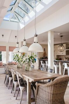 Open concept dining room with white industrial pendants hung from a skylight over the long, weathered farmhouse dining table