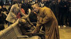 Pietà buddista Un monaco prega per un uomo deceduto alla stazione di Shanxi Taiyuan, in Cina (Credits: Reuters / Asianewsphoto)