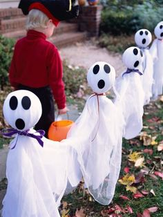 Friendly Ghosts ~ A row of goblins leads trick-or-treaters to your door. For each ghost, insert a 1/4-inch-diameter dowel into an 8-inch-diameter plastic-foam ball; glue to secure. Drive the other end of the dowel into the ground. Cut up both sides of a white garbage bag; lay it over the ball. Layer one yard of cheesecloth over the bag. Gather both materials below the plastic-foam ball and tie with a ribbon. Cut three ovals from adhesive-backed black felt and place on ghosts head. To make