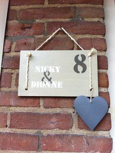 Stoer naambord van sloophout, bedrukt met huisnummer en namen.