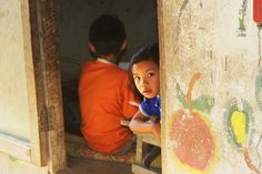 A child from the New Blood School for refugee children peeks out at the camera by Thai-Childrens-Trust, via Flickr