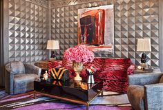 Wearstler squeezes in an orange and black Art Decco container to mix with her multi-colored rug, red and pink zebra patterned sofa in this vivid family room. Image courtesy Kelly Wearstler.