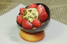 Une 1/2 sphère en chocolat garnie d'un crumble inversé fraises pistache, le tout délicatement posé sur un pain de Gênes moelleux