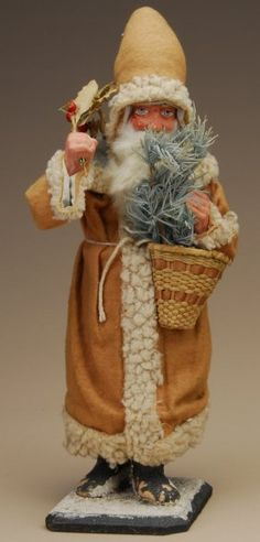 """14"""" German, ca. 1900, Santa candy container with original basket, holding holly in one hand.  Photo courtesy Dan Morphy Auctions"""