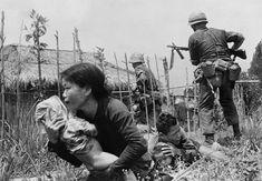 Una donna scappa con il figlio durante il fuoco di un cecchino nel villaggio di My Son, vicino a Da Nang, nell'aprile del 1965. - (Eddie Adams, Ap/Ansa)