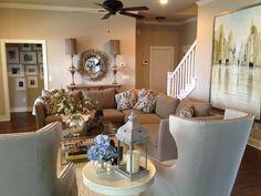 Gray, Monochromatic Living Room. Grey Sofa. Cream Living Room. IO Metro. Glass Coffee Table. Round Mirror. Gallery Wall. White Frames. Grey chairs. Cream Rug. Large Art.