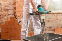 La construcción de concreto de mezcla o mortero trabajador con una batidora de mano Foto de archivo