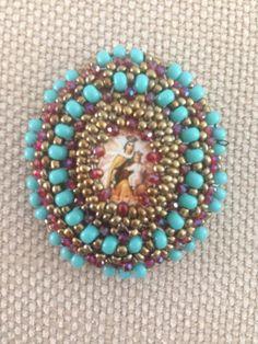 Medallón con imagen religiosa en colores turquesa y rojo muy hermoso