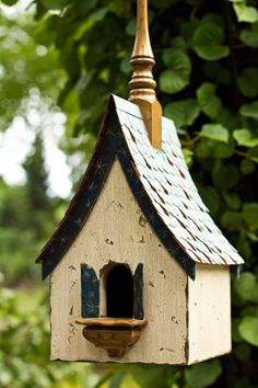The Starry Starry Night is a festive birdhouse decorated with a white wash house and blue trim and shutters with gold stars.