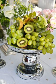 Pretty and simple centerpiece.  Grapes and Kiwis! Tuck in some pretty orchids and lime hydrangea, and some wired crystals! Beautiful simplicity.