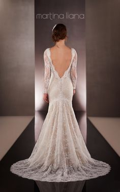 Discover more about this low back wedding dress that zips up under Lace-covered buttons with a fit-and-flare body and has vintage-inspired embroidered Lace over a matte-side Satin shell.