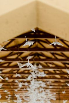 """Origami Bird Hanging Decor: Their beautiful wedding ceremony chapel venue was decorated with endless floating origami birds suspended from up above from """"rosyntjiebos"""" branches with grass lanes running down the aisle.    See more of this Rock Roses & Romance, South African Wedding here! ♥  ♥  ♥ Follow us on Facebook: www.facebook.com/confettidaydreams ♥  ♥  ♥ Rock Roses & Romance #Gauteng #Wedding #SouthAfrica #succulents #rustic Shot by #LouiseVorster"""
