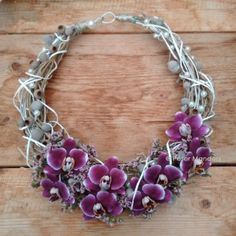 Complement your bridal bouquet with a piece of jewellery made of real flowers.  This pretty floral necklace with purple orchids and silver brunia would look stunning.  By Peter Manders at  http://www.bloemen.biz/bloemen/trouwen/