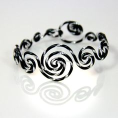 This bracelet is made out of anodized aluminum wire in shiny textured black and silver finish. I made and designed this piece to be adjustable and