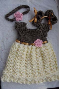 This listing is for a baby dress, maryjane and headband set. This dress is made out of a soft sparkly brown yarn with a cream colored bottom. The ribbon ties in the back and is an antique gold color. There is a little pink flower attached to the dress. The headband and shoes are made