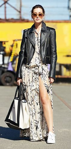 A floral maxi dress is paired with a leather motorcycle jacket, tote, white sneakers, and feminine sunglasses