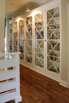 """Why waste space with plain hallways when you can add attractive, custom-built bookcases like this one, designed by Stacy Jacobi. Her design style has been described as """"New England Coastal went to Hollywood,"""" and we think this bookcase demonstrates that perfectly. Jacobi had the bookcase handmade by Mark Blaire, who used simple unfinished pine with glass panes, then painted it with Benjamin Moore high-gloss White Dove paint."""