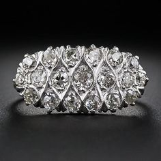 Nineteen bright and beautiful old mine-cut diamonds, together weighing one carat, glisten from an enchanting curvilinear fretwork design superbly rendered in platinum over 14 karat gold. This sparkling treasure, from the turn-of-the-twentieth-century (nineteen hundred, that is) gently curves across your finger and measures 3/4 of an inch long by 3/8 inch wide.