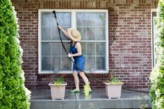 Housewife standing on a patio washing the windows of her house with a hose attachment as she spring-cleans the exterior at the start of the new summer season