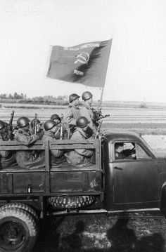 """Original caption:""""For Our Soviet Motherland"""", Soviet troops in truck with flag, 1943."""