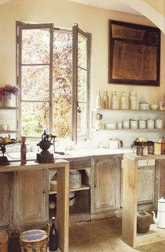 beautiful old country kitchen. Love the faded wood, wildflowers, old bottles and jars and the brightness of the room