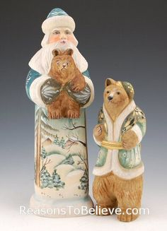 Bearing a Christmas Gift - Santa with Bears - 2 individual wood carvings. Santa joyfully holds a baby bear as his mother stands nearby.