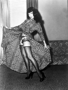 Frangetta bombata, sorriso malizioso, biancheria intima sexy e pose provocanti: ecco le caratteristiche che per decenni hanno alimentato il mito di Betty Page, madre di tutte le pin-up e simbolo dell'immaginario erotico anni Cinquanta. Milano le rende omaggio con la mostra 'Betty Page trentadu