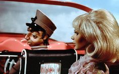 Lady Penelope in her iconic pink Rolls Royce convertible, being driven by Parker with the roof down. Thunderbirds by Gerry and Sylvia Anderson
