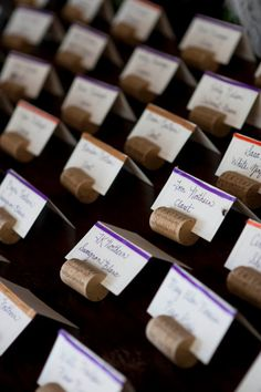 wedding place cards in wine corks and colored ribbons according to meal ordered