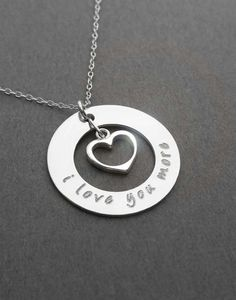 A sterling silver washer necklace  hand stamped to say i love you more.