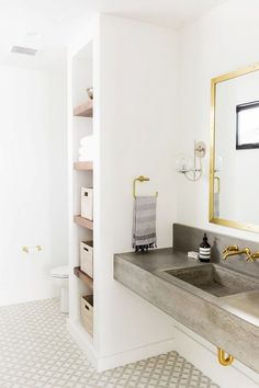 Bright, modern bathroom with a concrete sink, a gold mirror, and printed tile floors