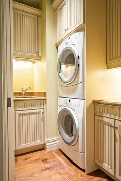A smaller laundry room with light hardwood floors and striped-front cream cabinetry. The front loading washer and dryer are tucked into a nook next to the sink.