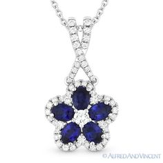 The featured pendant is cast in 14k white gold and showcases a flower design made up of a round cut diamond center, oval cut blue sapphire petals, and round cut diamond accents paved throughout the flower outline and on the bale.