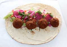 Falafel Sandwich with pickled turnips, lettuce, tomatoes, onions and parsley.