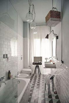 Tout en longueur, cette salle de bains mise sur les carreaux de ciment, au sol, et le carrelage métro, au mur