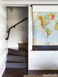 In a Marin County, California, beach house designed by Erin Martin and Kim Dempster, a vintage pull-down map bought on eBay hides the TV.   - HouseBeautiful.com