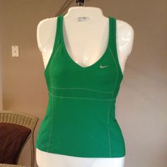 Nike Fit Dry Top Comfortable and stylish work out top. Nike Fit Dry work out shirt is green.  Size XS. The length is 20.5.  Laying flat Arm to Arm is 13.5.  Fits great. This item is in Good condition, Authentic and from a Smoke And Pet free home. All Offers through the offer button ONLY. I Will not negotiate Price in the comment section. Thank You😃 Nike Tops