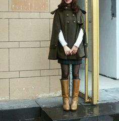 Army green cape coat, plaid skirt, Swiss dot stockings, brown camel boots.