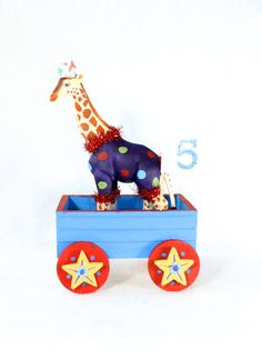 Small Circus Wagon in Blue. Party decoration by PaintedParade, $19.00. Fun table decoration, a personal animal wagon. A couple of these down the center of a table would be cute. Comes with white flag that has age on it. Cute on food table as well.