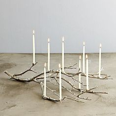 This is a manufactured metal candelabra, but I could see making one from a sturdy branch and some metallic paint. Use that sticky wax stuff to adhere the candles to the branch.