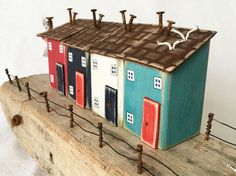 Statement driftwood art piece featuring little houses made from recycled wood and arranged in a harbour scene on a fabulous driftwood base. This large coastal art piece would make a wonderful wedding gift or luxury gift for a birthday or retirement gift for the lover of recycled art or salvaged art. The base is constructed of an interesting stepped piece of driftwood, which seemed to lend itself to becoming a harbour piece and a tiny ramp of driftwood leads to the sea. Four houses are made…