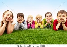 by pressmaster (Image of happy boys and girls lying on a green grass)