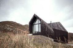 Raw Architecture Workshop est un studio d'architecture londonien qui est à l'origine de cette maison familiale construite dans les Highlands écossais.  Cette habitation de trois étages est dessinée principalement avec des formes anguleuses qui tranchent avec les formes organiques des collines environnantes. L'utilisation d'un revêtement sombre en bois font que la construction se mêle aux tons rugueux de la nature.
