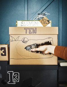 Kartonnen doos met een krokodil erop getekend en een hand die een cadeautje uit de muil wil halen